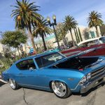 Blue Chevelle with Hood open next to palm tree